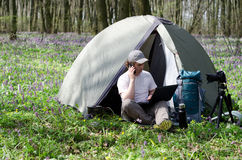 Man photographer working outdoors in a tent camp. Stock Images