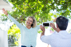 Man photographing cheerful woman against trees Stock Images