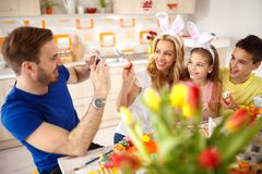 Man photographing family while painting eggs stock image