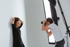 Man photographing female model in professional studio. With equipment Stock Images