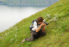 Man photographing flower in the green slope Royalty Free Stock Photography