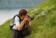 Man photographing flowers in the green slope of summer Soroya Stock Photo