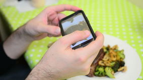 Man photographing food at restaurant with his phone stock video