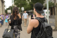 Man photographing girl on street Stock Image