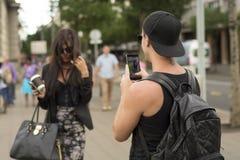 Man photographing girl on street stock image