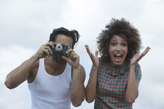 Man photographing with girlfriend standing beside him Royalty Free Stock Photos