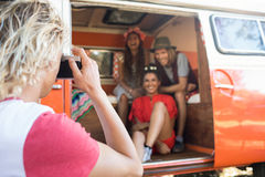 Man photographing happy friends sitting in camper van Stock Images