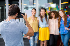 Man photographing his female colleagues with camera Stock Images