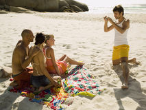 Man photographing his friends on the beach. Royalty Free Stock Images