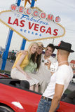 Man Photographing His Friends Sitting On Car. Middle aged men photographing his friends sitting on car with 'Welcome To Las Vegas' sign in the background Stock Photography