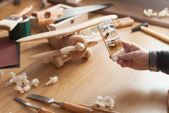 Man photographing his handmade wooden toy. Airplane with a smart phone on a work table Royalty Free Stock Photo