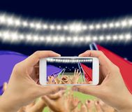 Photographing victory. Man photographing his team`s victory with a smartphone of the football stadium .The screen content is designed by me and not is Stock Photography