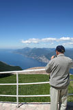 Man Photographing Lake Garda. A man is taking a photograph of lake Garda fron a nearby mountain royalty free stock photo