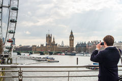 Man photographing London skyline. Rear view of man photographing skyline of London city, looking towards the Eye ad Palace of Westminster, England royalty free stock image