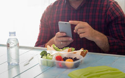 Man photographing lunch box with healthy food. Copy space Stock Photos