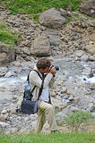 Man photographing near the mountain stream Royalty Free Stock Images