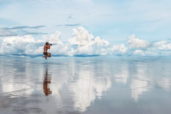 Man photographing ocean. Reflections of clouds on the water surface Stock Photos