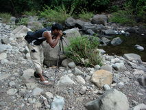 Man photographing river. Side view of young man photographing river in countryside Royalty Free Stock Photo