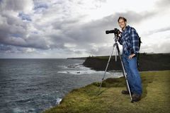Man photographing scenery in Maui, Hawaii. Caucasian mid-adult male standing with camera on tripod looking at viewer on cliff overlooking the ocean in Maui Stock Images