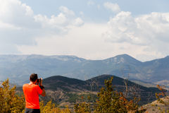 Man photographing scenic mountain landscape Royalty Free Stock Images