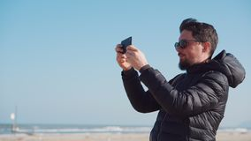 Man is photographing seascapes by mobile phone. On beach in sunny day stock footage
