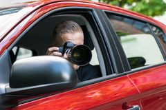 Man photographing with slr camera from car Stock Images