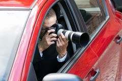 Man photographing with slr camera from car Stock Photos