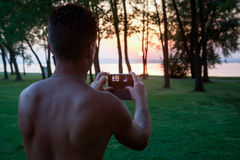 Man photographing sunset with mobile phone Stock Photography