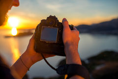 Man photographing sunset on the top of mountain Stock Image