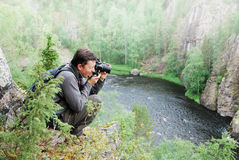 Man photographing on the top of taiga forest. Royalty Free Stock Photography