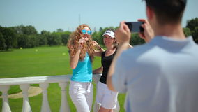 The man photographing two girls near the course stock footage