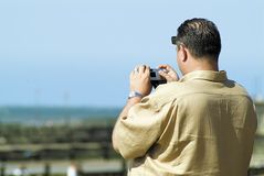 Man photographing view. Rear view of middle aged man taking picture of view with digital camera stock photo