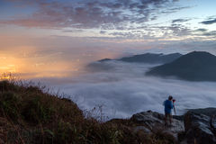 Man photographing the view from Lantau Peak at dawn. Man photographing the lights of Tung Chung New Town below clouds on Lantau Island. Viewed from the Lantau Stock Photo