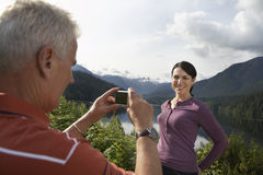 Man Photographing Woman Against The Mountains Royalty Free Stock Photos