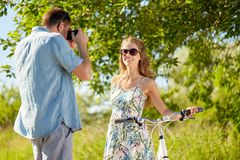 Man photographing woman with bicycle by camera Royalty Free Stock Photography