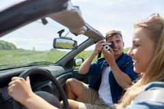 Man photographing woman driving car by film camera Royalty Free Stock Images