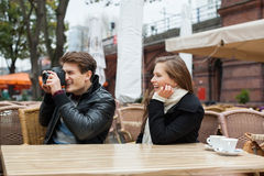 Man Photographing With Woman At Outdoor Restaurant Royalty Free Stock Photos
