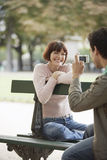 Man Photographing Woman On Park Bench Royalty Free Stock Photo
