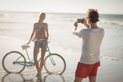 Man photographing woman standing by bicycle at beach Royalty Free Stock Image
