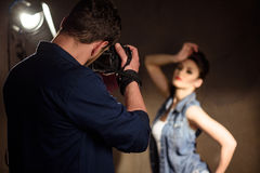Man photographing woman in studio Stock Image