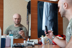 Man photographs herself in the mirror Royalty Free Stock Image