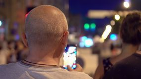 The man photographs the night city on the smartphone. Close-Up Woman Using Smart-Phone In The City stock video footage