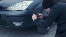 The man photographs on phone scratches by car. The man photographs scratches by car using phone stock footage