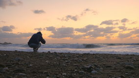 The man photographs the sea sunset stock footage
