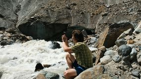 Man photographs on a smartphone landscape - mountain river, a glacier stock images