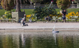 Man photographs toy sailboat on pool in Luxembourg Garden, Paris, France. Man aims camera at toy sailboat in the round pool in the Luxembourg Garden, Paris Royalty Free Stock Photography