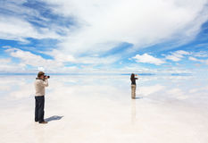 Man photographs woman who takes pictures of landscape Royalty Free Stock Photo