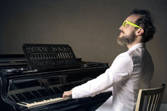 Man with piano. Crazy man with white suit playing the piano Royalty Free Stock Photography