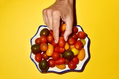 Free Man Picking A Cherry Tomato From A Plate Stock Photos - 109749503