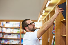 Man picking a book in a library. Young man with glasses picking a book in a library Royalty Free Stock Image